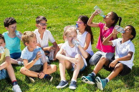 Photo pour Happy children drinking water after running in park outdoors at sunny day - image libre de droit