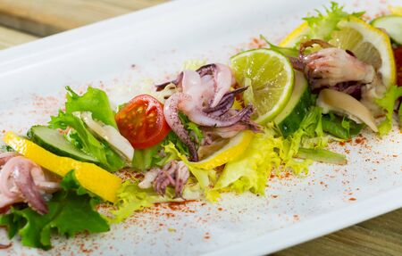 Salad with boiled squid, mix salad, lime and smoked paprika