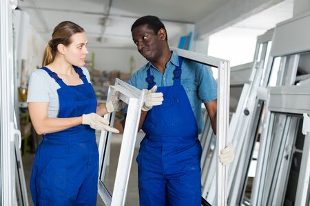 Portrait of man and woman worker who are conflicting with window frames in the pvc workshop.