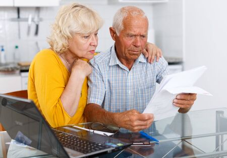 Foto de Worried mature couple with documents near laptop in home interior - Imagen libre de derechos