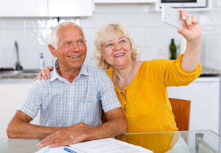 Photo pour Smiling senior family couple taking selfie on mobile phone at home - image libre de droit