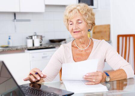 Photo pour Senior woman sitting and filling up documents at kitchen table - image libre de droit