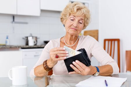 Photo for Senior woman is upset because of she has little money - Royalty Free Image