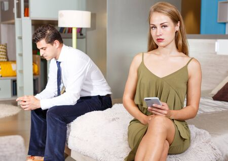 Photo pour Relationship difficulties. Upset young woman sitting on bed with phone on background with frustrated boyfriend - image libre de droit