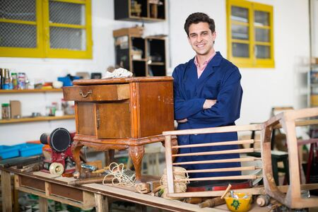 Portrait of an expert in restoration of antique furniture in workroom