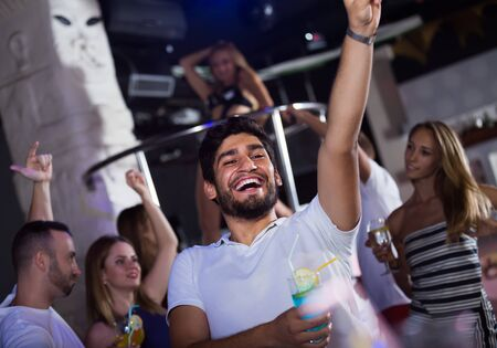 Photo pour positive man joying and dancing on party in the club with cocktail - image libre de droit