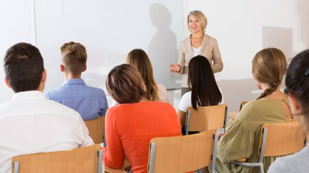 Foto de Elegant female teacher lecturing to students in auditorium - Imagen libre de derechos