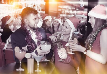 Cheerful guy with two girls funning and toasting drinks on a new year eve party in the bar