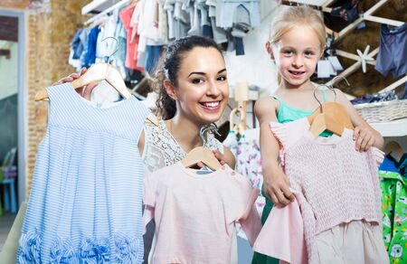 portrait of happy woman and girl shopping kids apparel in clothes store