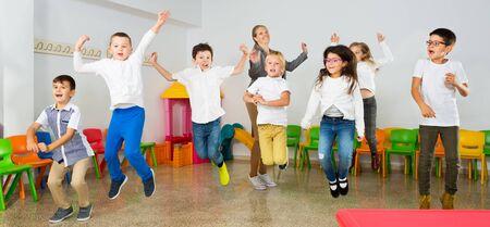 Foto de Group of happy cheerful children with their female teacher jumping together at schoolroom - Imagen libre de derechos