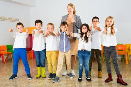 Photo pour Portrait of happy cheerful positive smiling female teacher with her happy schoolkids in classrom - image libre de droit