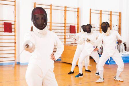 Foto de active woman fencer practicing fencing combination in training room - Imagen libre de derechos
