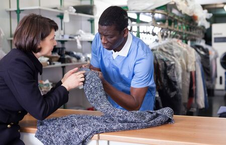 Photo pour Manager of laundry working with woman client, receiving clothing for dry cleaning - image libre de droit