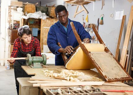 Photo pour Portrait of male and female restorers working with wooden furniture in workshop - image libre de droit