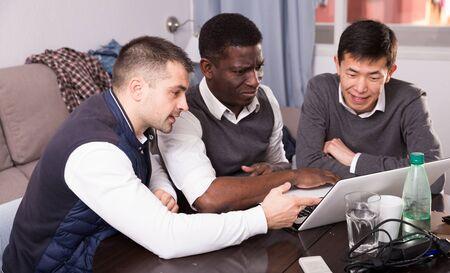 Photo pour Cheerful male friends using laptop during bachelor gathering at home - image libre de droit
