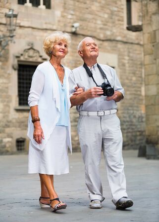 Photo for Happy cheerful positive smiling mature couple on traveling together, photographing city attractions with camera - Royalty Free Image