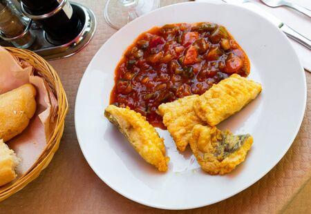 Foto de Flour-fried cod fish served with ratatouille – Spanish fish dish - Imagen libre de derechos