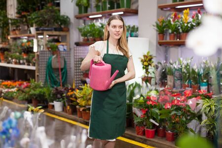 Photo for Woman florist working in floral shop; watering flowers from a plastic watering can - Royalty Free Image