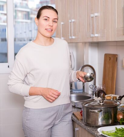 Photo for Portrait of housewife who is standing in time cooking in the kitchen at her home. - Royalty Free Image