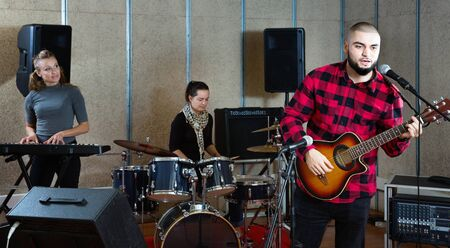 Photo for Rehearsal of music band. Happy cheerful  guy guitar player and singer practicing with band members in recording studio - Royalty Free Image