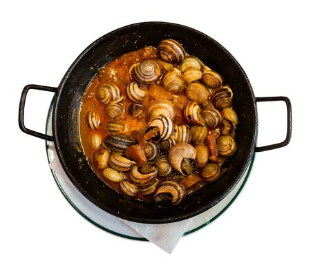 Foto de Top view of black frypan with traditional Spanish tapa Caracoles en salsa - snails stewed to homemade in gravy. Isolated over white background - Imagen libre de derechos