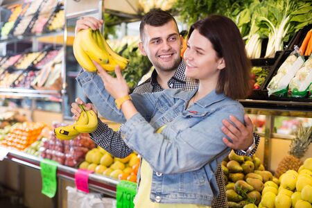 Foto für Young loving couple deciding on fruits in grocery shop - Lizenzfreies Bild