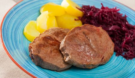 Delicious veal Medallions de cadera with boiled potato and red sauerkraut