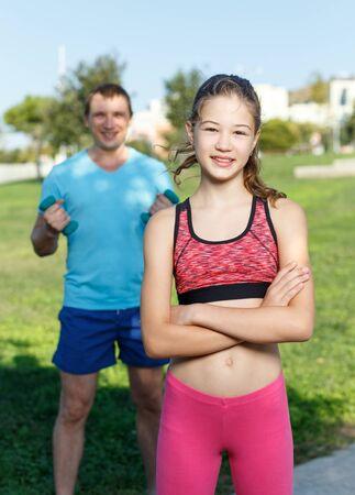 Foto de Portrait of happy slim tweenager girl standing on outdoor sports ground, ready for workout with her father - Imagen libre de derechos