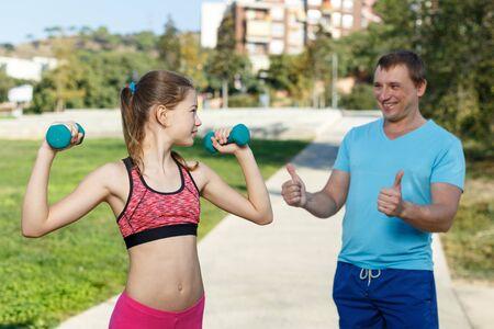 Foto de Sporty preteen girl exercising with dumbbells while father controlling process of training - Imagen libre de derechos