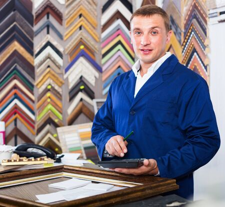 Photo pour Cheerful  positive diligent man worker holding picture frame details on counter in studio - image libre de droit
