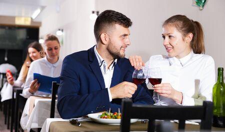Photo pour Romantic couple is having dinner in the restaurante indoor. - image libre de droit