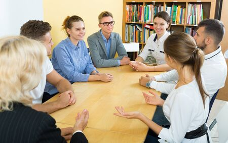 Photo pour Students doing team study together in  classroom,  sitting at table - image libre de droit