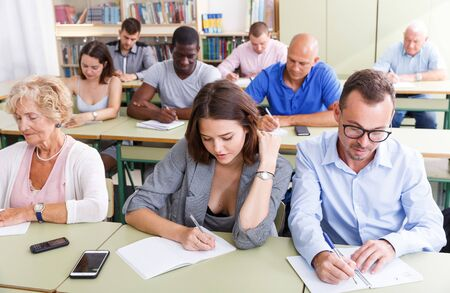 Photo pour Students mixed age listening task for exam in the classroom - image libre de droit