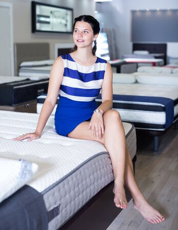 Photo pour Female is sitting on mattress for testing it in the store. - image libre de droit