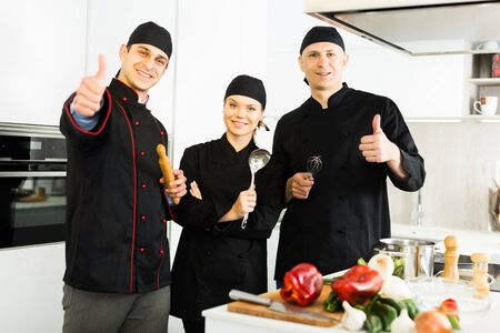 Photo for Three young cooks wearing black uniform showing thumbs up on kitchen - Royalty Free Image