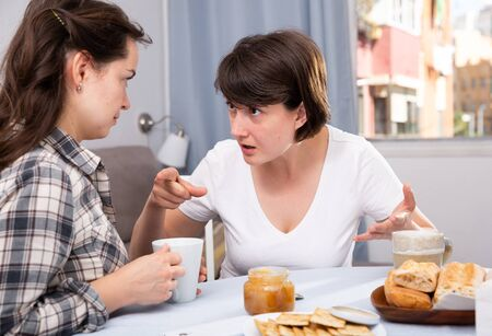 Photo pour Emotional women having conflict at table with coffee  in home interior - image libre de droit