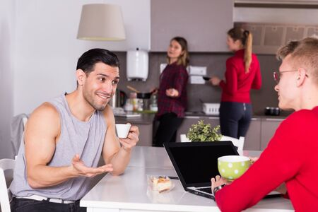Foto per Positive man with cup of coffee talking to guy sitting in kitchen of hostel with laptop - Immagine Royalty Free