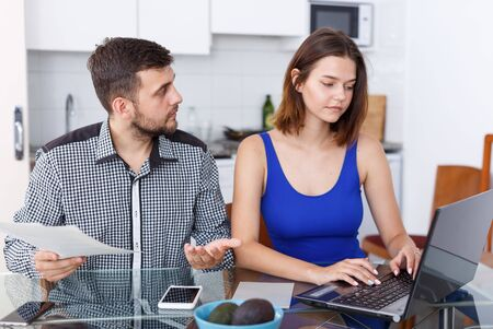 Photo pour Serious young man and woman with financial documents near laptop at home - image libre de droit
