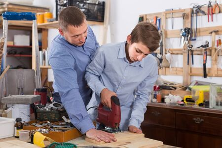 Foto de happy italian father and son with  fret saw cutting wood plank in  garage - Imagen libre de derechos