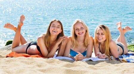 Photo for Portrait of three happy young women wearing swimsuits having fun together on beach - Royalty Free Image