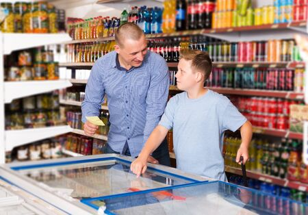 smiling father doing shopping with boy looking at shopping list while choosing fresh products in food store