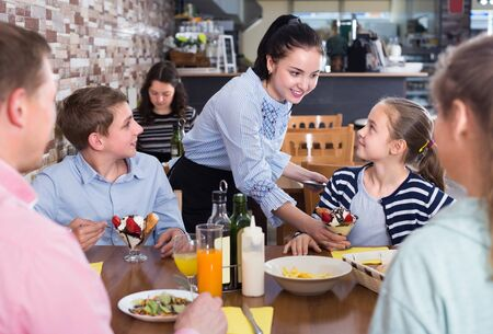 Photo for Polite nice waitress serving dishes to family in cafe - Royalty Free Image