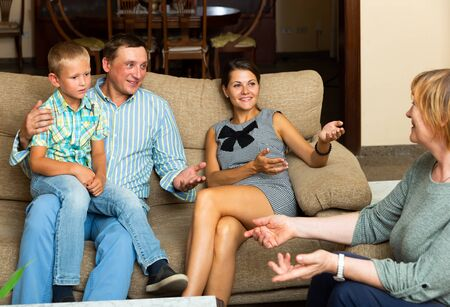 Adult man with wife and preteen son visiting his elderly mother at home, cheerfully talking together on sofaの写真素材