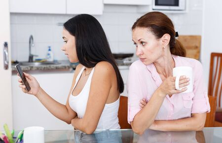 Photo pour Young girl using her smartphone at kitchen table, her mother are near her - image libre de droit