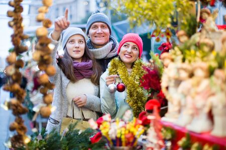 Photo pour Happy family of three choosing Christmas decoration at  Christmas market - image libre de droit