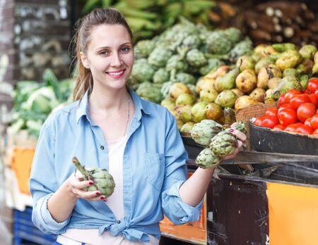 Foto für Portrait of positive woman who is choosing artichokes in the market - Lizenzfreies Bild