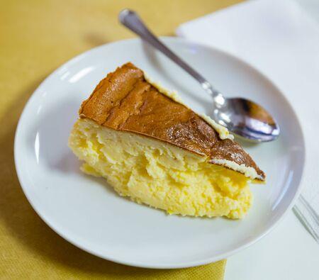 Photo pour Sweet cream cheese dessert. Slice of spanish cheesecake Tarta de queso on white plate - image libre de droit
