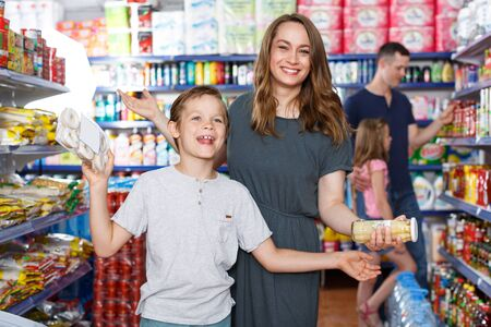 Photo pour Emotional mother and son with meal for home, family in the supermarket - image libre de droit