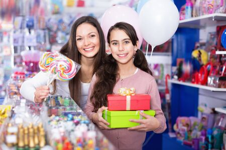 Photo pour Happy cheerful positive female and girl with gifts and balloons in the candy store - image libre de droit