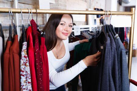 Photo pour Positive cute girl customer buying fashion shirt  in the  shop - image libre de droit